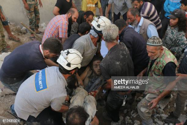 TOPSHOT Syrian civil defence volunteers known as the White Helmets hold the body of a young man after he was pulled from the rubble following a...