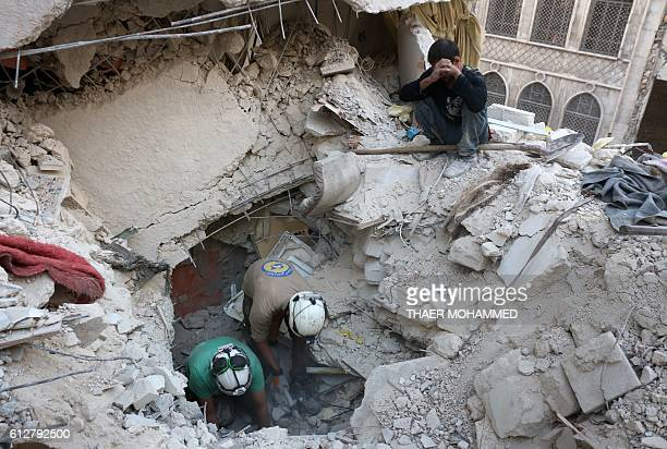 TOPSHOT Syrian civil defence volunteers known as the White Helmets search for victims amid the rubble of destroyed buildings following a government...