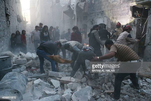 Syrian Civil Defence workers and pedestrians clear debris after an alleged air strike by Syrian government forces in the Bab alNairab neighboured the...