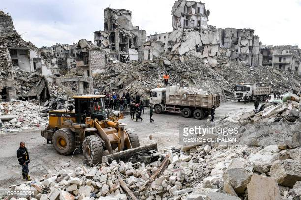 Syrian civil defence workers clear the rubble of a collapsed fivestorey building in the Salah alDin district of the northern city of Aleppo on...