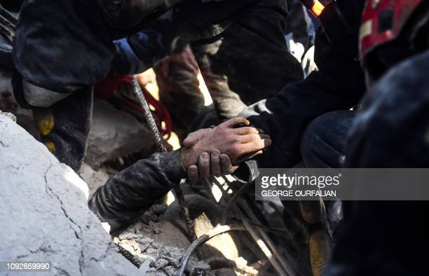 TOPSHOT Syrian civil defence workers rescue a child from under the rubble of a collapsed fivestorey building in the Salah alDin district of the...