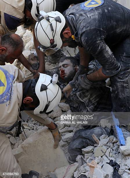 Syrian Civil Defence workers try to pull a man out from under the rubble of a building following a reported airstrike by government forces on May 24...
