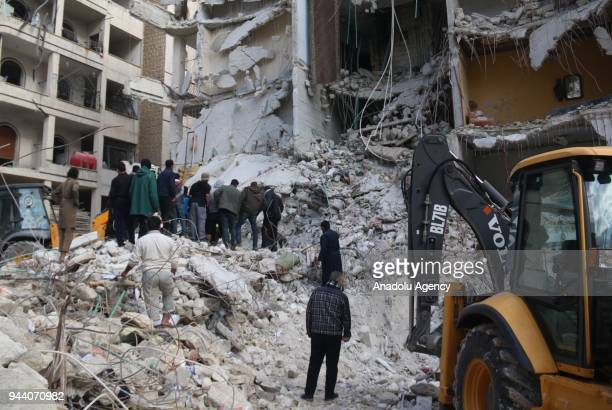 Syrian civil defense members conduct search and rescue operations at the site of the blast that leveled a sevenstory building after an explosion that...
