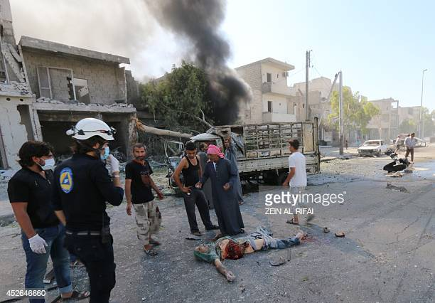A Syrian civil defense worker and civilians stand next to a body after a Syrian government helicopter allegedly dropped a barrel bomb on the Sakhour...