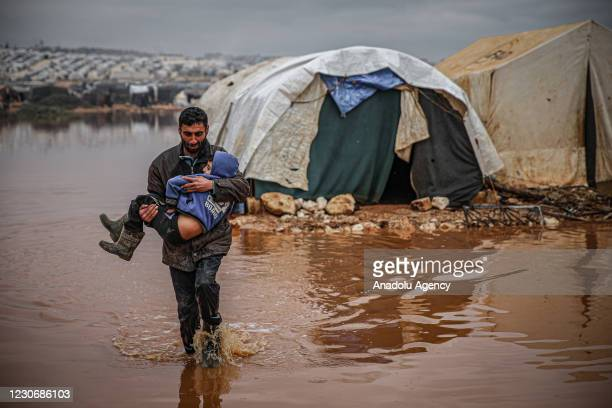 Syrian civilian carries a child as they evacuate their belongings from flooded tents at the Kefer Lusin refugee camp after heavy rain caused floods...