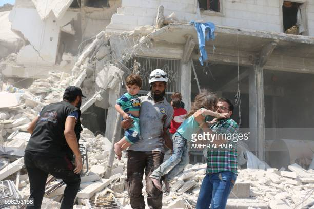 Syrian civilians and a rescue worker evacuate children in the Maadi district of eastern Aleppo after regime aircrafts reportedly dropped...