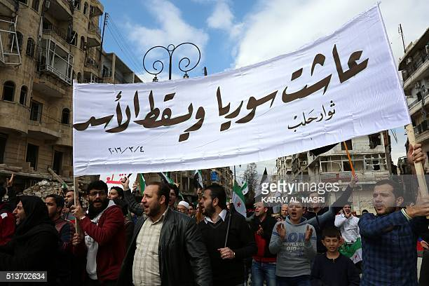 Syrian civilians and activists hold a banner reading in Arabic Long live Syria down with Assad during an antiregime demonstration in the...