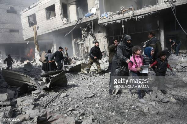 Syrian civilians and children run for cover amid the rubble of buildings following government bombing in the rebel-held town of Hamouria, in the...