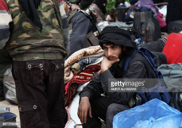 TOPSHOT Syrian civilians and rebel fighters arrive in the village Mizanz some 30 kilometres northeast of Idlib on March 24 2018 after being evacuated...