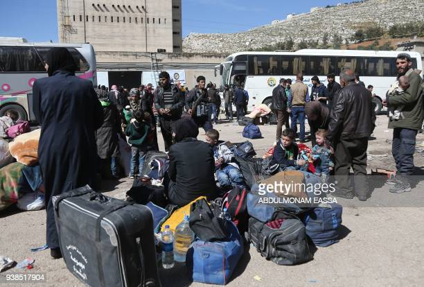 Syrian civilians and rebel fighters evacuated from Eastern Ghouta arrive in the village of Qalaat alMadiq some 45 kilometres northwest of the central...