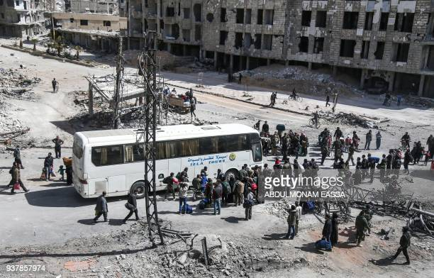 Syrian civilians and rebel fighters prepare to embark aboard a bus during the evacuation from the town of Arbin in the Eastern Ghouta region on the...