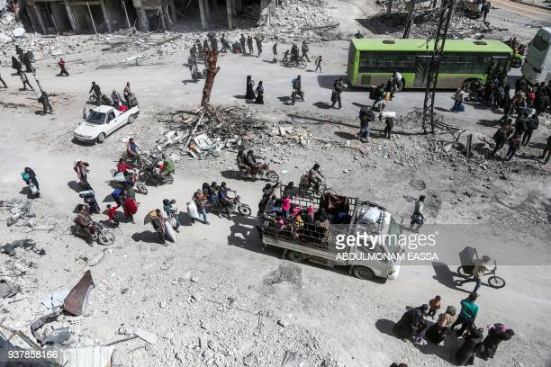 Syrian civilians and rebel fighters prepare to embark aboard buses during the evacuation from the town of Arbin in the Eastern Ghouta region on the...