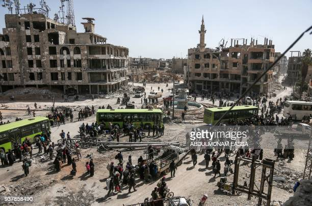 TOPSHOT Syrian civilians and rebel fighters prepare to embark aboard buses during the evacuation from the town of Arbin in the Eastern Ghouta region...