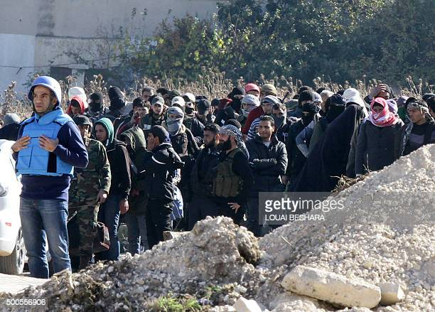Syrian civilians and rebel forces wait for the buses as they began evacuating the last oppositionheld district of Waer in the central city of Homs...