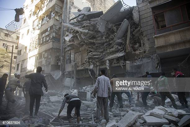 TOPSHOT Syrian civilians and rescuers gather at site of government forces air strikes in the rebel held neighbourhood of AlShaar in Aleppo on...