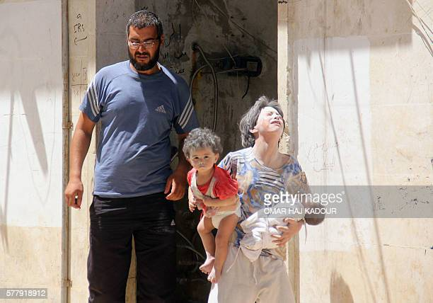 TOPSHOT Syrian civilians are seen following a reported air strike by Syrian government forces on the rebelheld northwestern city of Idlib on July 20...