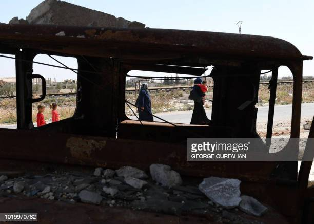 TOPSHOT Syrian civilians are seen through a burned vehicle enter the Abu Duhur crossing on the eastern edge of Idlib province on August 20 2018...