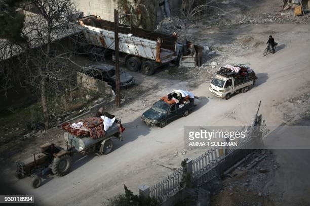 Syrian civilians carry their belongings as they flee following government bombardment on Kafr Batna in the besieged Eastern Ghouta region on the...