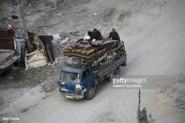 Syrian civilians carry their belongings on the back of a pick up truck as they flee following government bombardment on Kafr Batna in the besieged...