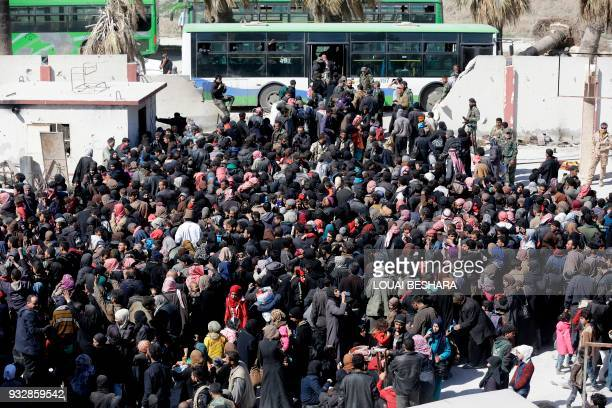 TOPSHOT Syrian civilians evacuated from rebelheld areas in the Eastern Ghouta gather at a school in the regimecontrolled Hosh Nasri on the...