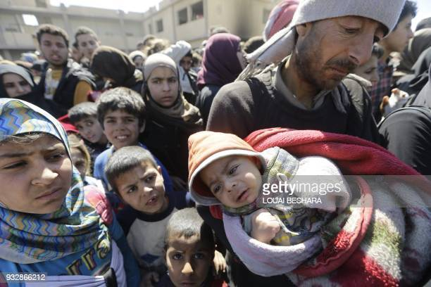 Syrian civilians, evacuated from rebel-held areas in the Eastern Ghouta, gather at a school in the regime-controlled Hosh Nasri, on the northeastern...