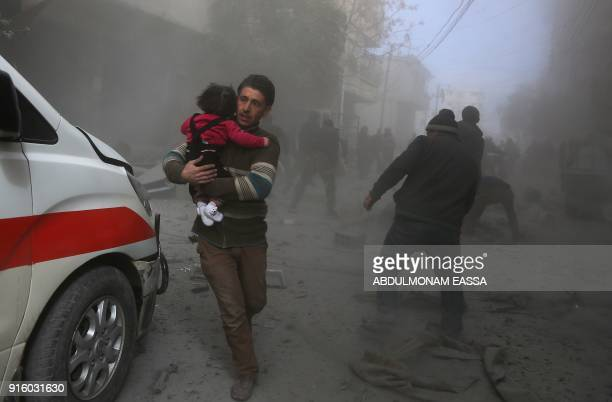 Syrian civilians flee from reported regime air strikes in the rebel-held town of Saqba, in the besieged Eastern Ghouta region on the outskirts of the...