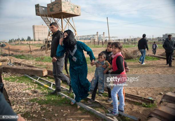 Syrian civilians flee from the village of Ras alAyn Syria after two jets bombed the village sending people fleeing into neighboring Ceylanpinar...