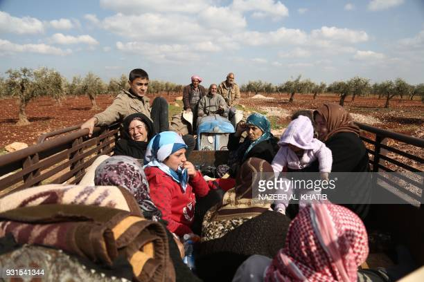 TOPSHOT Syrian civilians fleeing Afrin after Turkey said its army and allied rebels surrounded the Kurdish city in northern Syria pass through the...