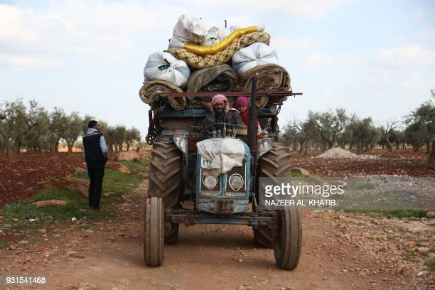 Syrian civilians fleeing Afrin after Turkey said its army and allied rebels surrounded the Kurdish city in northern Syria pass through the village of...