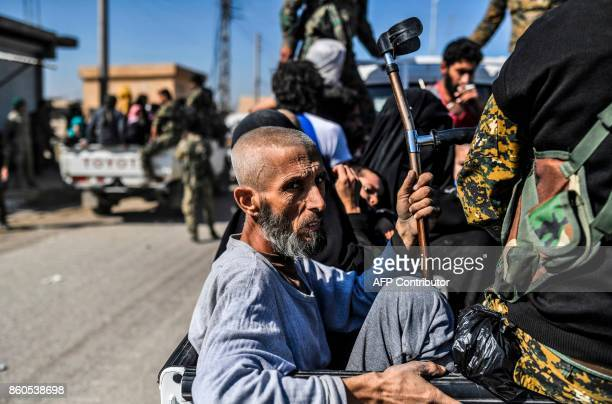 TOPSHOT Syrian civilians gather on the western front after fleeing the centre of Raqa on October 12 2017 Syrian Democratic Forces Syrian fighters...