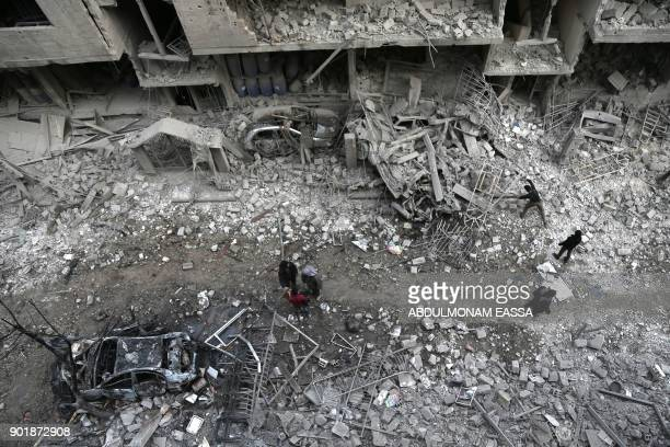 TOPSHOT Syrian civilians inspect the damage following reported bombardment by Syrian and Russian forces in the rebelheld town of Hamouria in the...