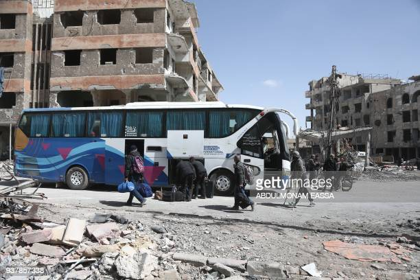 Syrian civilians load their belongings on to a bus prior to evacuating from the town of Arbin in the Eastern Ghouta region on the outskirts of the...