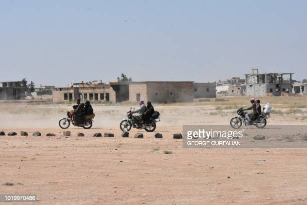 Syrian civilians on motorcycles enter the Abu Duhur crossing on the eastern edge of Idlib province on August 20 2018 Civilians are coming from...