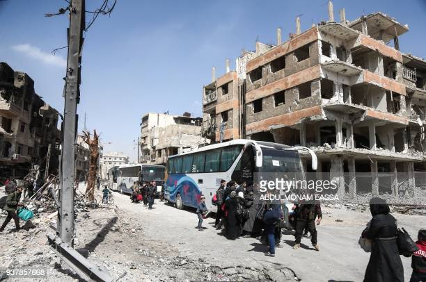 Syrian civilians prepare to embark aboard a bus during the evacuation from the town of Arbin in the Eastern Ghouta region on the outskirts of the...