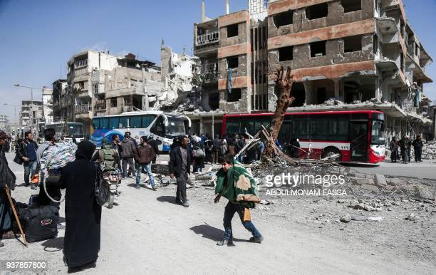 Syrian civilians prepare to embark aboard buses during the evacuation from the town of Arbin in the Eastern Ghouta region on the outskirts of the...