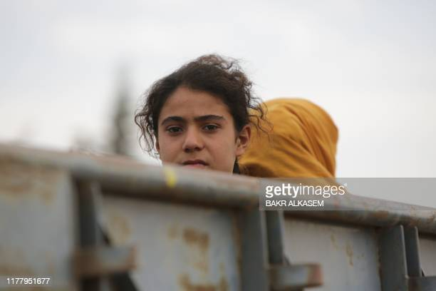 Syrian civilians ride in the back of a truck as they flee villages where fighting continues in the countryside of Tal Abyad, as Turkey-backed...