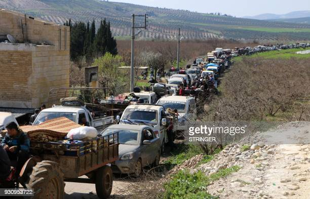 TOPSHOT Syrian civilians ride their cars through Ain Dara in Syria's northern Afrin region as they flee Afrin city on March 12 2018 amid battles...