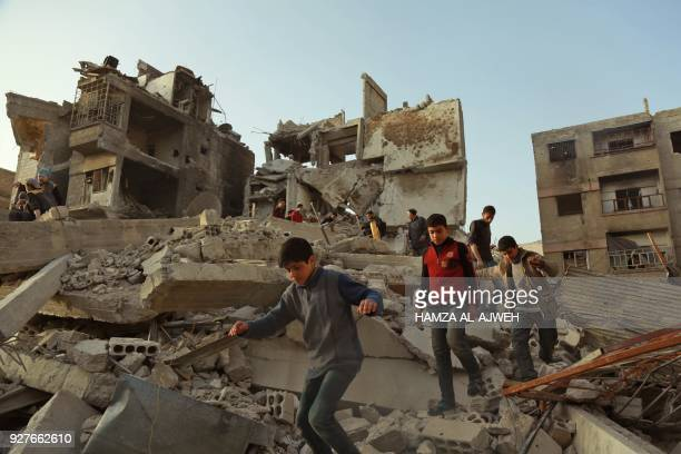 TOPSHOT Syrian civilians walk above the rubble of destroyed buildings in the rebel enclave of Eastern Ghouta on March 5 2018 on the outskirts of...