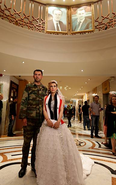 A Syrian Pose For Photo Under Portraits Of President Bashar Al Ad