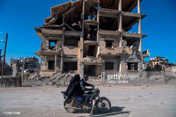 Syrian couple rides a motorcycle past a destroyed building in the Islamic State group's former Syrian capital of Raqa in northern Syria, on February...