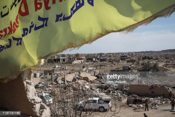 Syrian Defence Force flag flies over the destroyed ISIL encampment on March 23, 2019 in Baghouz, Syria. The Kurdish-led and American-backed Syrian...