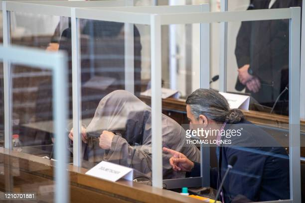 Syrian defendant Eyad al-Gharib hides himself under his hood prior to a trial against two Syrian defendants accused of state-sponsored torture in...