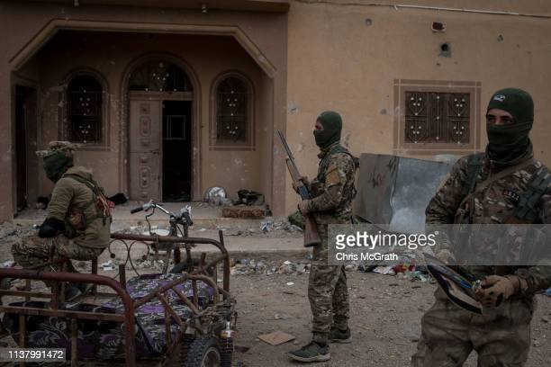 Syrian Democratic Firces fighters are seen in front of a building at a position in the final ISIL encampment on March 24, 2019 in Baghouz, Syria. The...