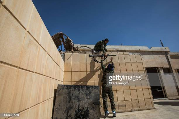 Syrian Democratic Force fighters hand off an RPG to be fired at the National Hospital a key position which was held by Islamic State jihadists along...
