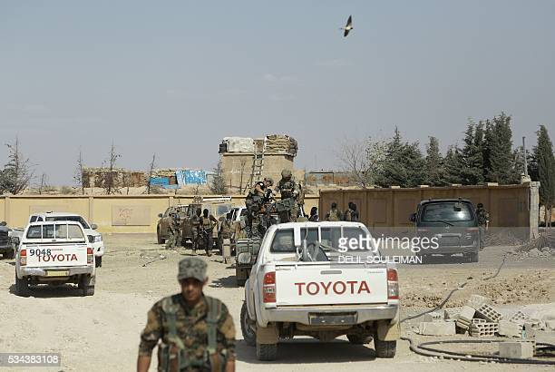 Syrian Democratic forces and armed men identified by them as US special operations forces are seen in the village of Fatisah in the northern Syrian...