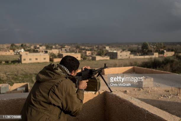 Syrian Democratic Forces commander fires at a suspected ISIL position from a rooftop near the front line on February 10 2019 in Bagouz Syria USled...