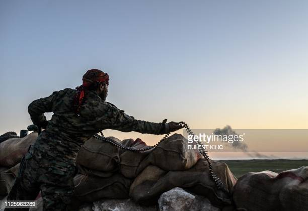 Syrian Democratic Forces fighter arranges an ammunition belt in a hilltop near the embattled village of Baghouz in Syria's northern Deir Ezzor...