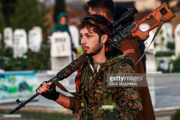 A Syrian Democratic Forces' fighter holds a sniper rifle on his shoulder as he attends the funeral of a slain Kurdish commander in the northeastern...