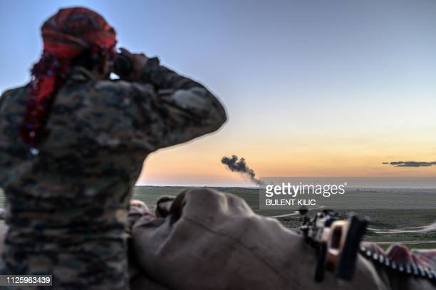 Syrian Democratic Forces fighter uses a binocular to inspect the embattled village of Baghouz in Syria's northern Deir Ezzor province on February 19...