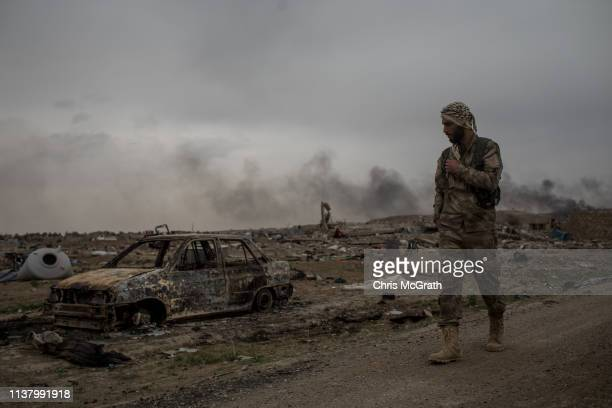 Syrian Democratic Forces fighter walks past destroyed vehicles in the final ISIL encampment on March 24 2019 in Baghouz Syria The Kurdishled and...